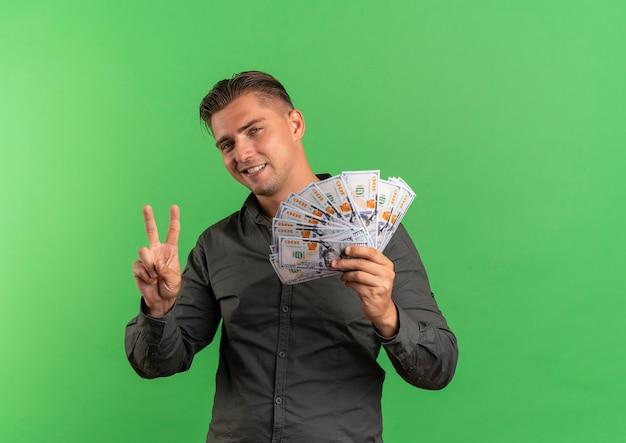 Молодой улыбающийся блондин красавец держит деньги и жесты знак победы рукой, изолированные на зеленом фоне с копией пространства