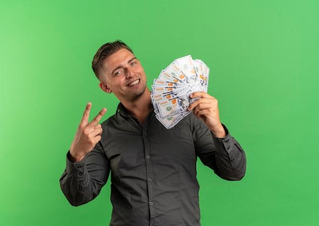 Молодой улыбающийся белокурый красавец держит деньги и жесты рукой знак победы, изолированные на зеленом пространстве с копией пространства
