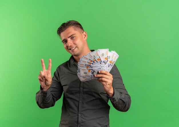 Young smiling blonde handsome man holds money and gestures victory hand sign isolated on green background with copy space