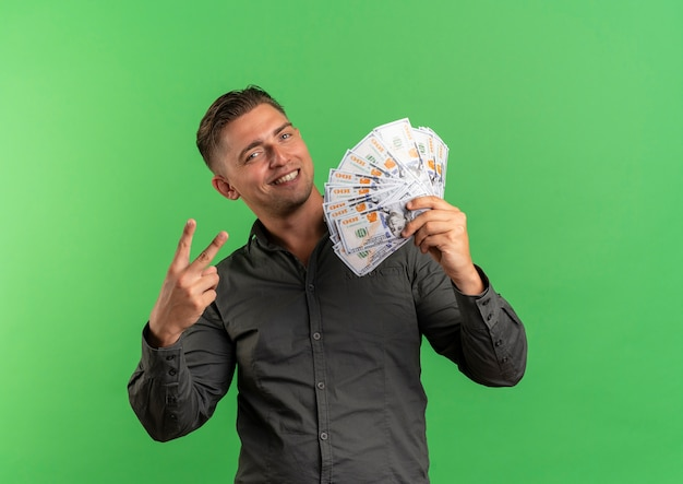 Young smiling blonde handsome man holds money and gestures victory hand sign isolated on green space with copy space