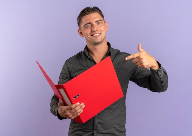 Il giovane uomo bello biondo sorridente tiene e indica la cartella di file isolata sullo spazio viola con lo spazio della copia