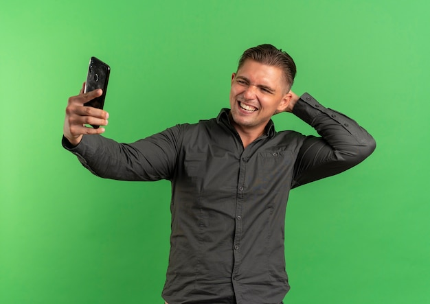 Young smiling blonde handsome man looks at phone taking selfie holding hand on neck behind isolated on green space with copy space