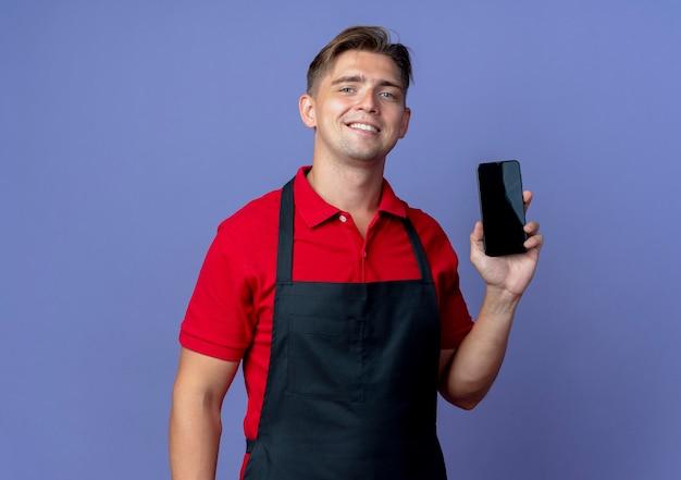 제복을 입은 젊은 웃는 금발의 남성 이발사는 복사 공간이있는 보라색 공간에 고립 된 전화를 보유하고 있습니다.