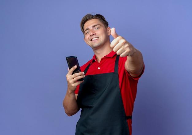 제복을 입은 젊은 웃는 금발의 남성 이발사는 보라색 배경에 고립 된 전화 엄지 손가락을 보유하고 있습니다.