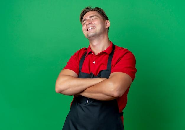 제복을 입은 젊은 웃는 금발의 남성 이발사는 복사 공간이있는 녹색 공간에 고립 된 교차 팔을 의미합니다.