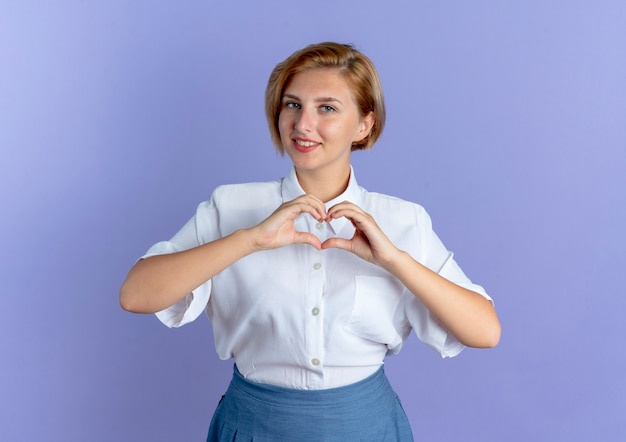 Giovane ragazza russa bionda sorridente gesti il segno della mano del cuore isolato su priorità bassa viola con lo spazio della copia