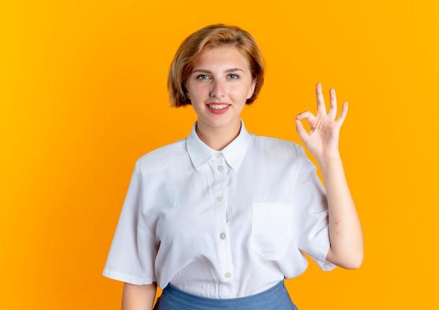 젊은 미소 금발 러시아 여자 제스처 확인 손 기호 복사 공간 오렌지 배경에 고립