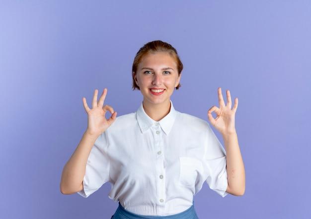젊은 미소 금발 러시아 여자 제스처 복사 공간 보라색 배경에 고립 된 두 손으로 확인 손 기호