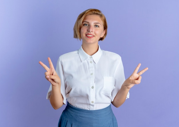 젊은 미소 금발 러시아 여자 제스처 복사 공간 보라색 배경에 고립 된 양손으로 승리 손 기호