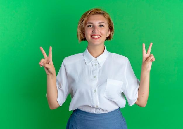 복사 공간 녹색 배경에 고립 된 두 손으로 젊은 웃는 금발 러시아 여자 제스처 승리 손 기호