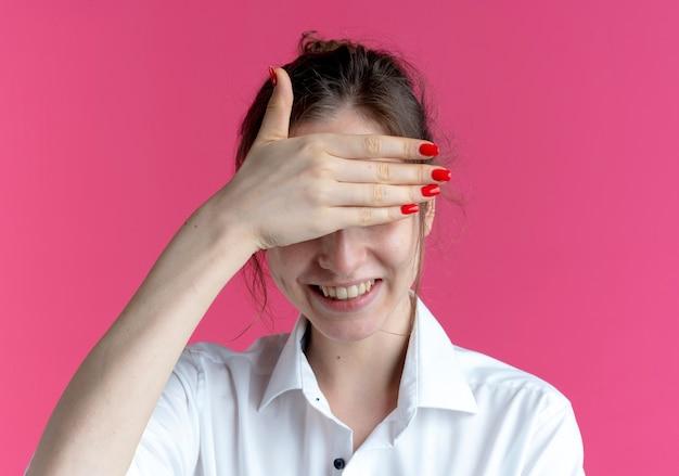 젊은 웃는 금발 러시아 여자 복사 공간이 분홍색 공간에 고립 된 손으로 눈을 숨 깁니다