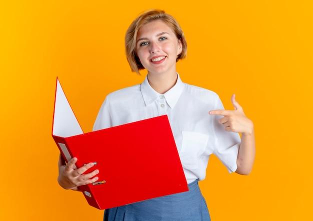 Молодая улыбающаяся русская блондинка держит и указывает на папку с файлами