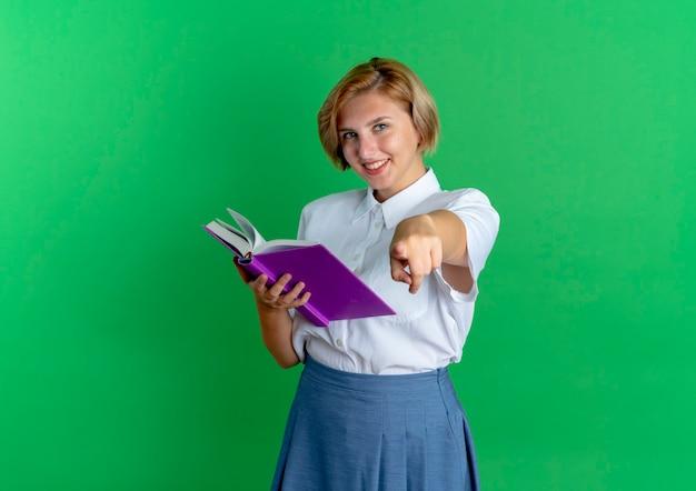 Молодая улыбающаяся русская блондинка держит книгу и указывает на камеру, изолированную на зеленом фоне с копией пространства