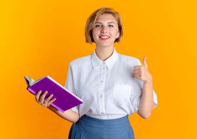 Молодая улыбающаяся русская блондинка держит книгу и большие пальцы руки вверх изолированы на оранжевом фоне с копией пространства