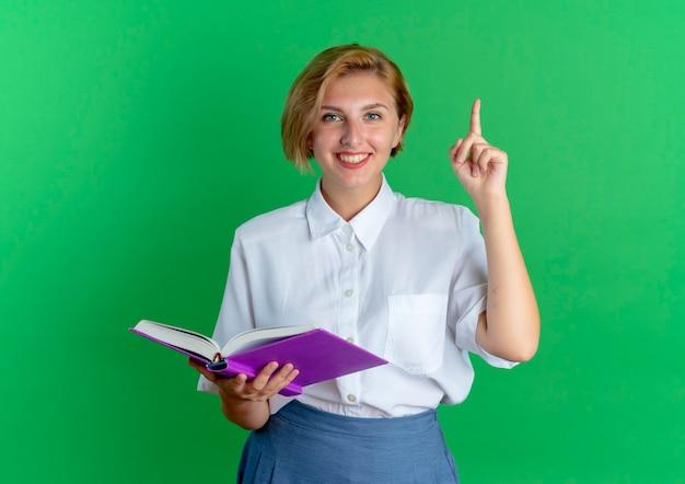 Молодая улыбающаяся русская блондинка держит книгу, направленную вверх, изолированную на зеленом фоне с копией пространства