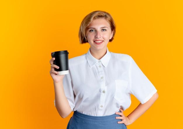 Молодая улыбающаяся русская блондинка держит чашку кофе, кладет руку на талию, изолированную на оранжевом фоне с копией пространства