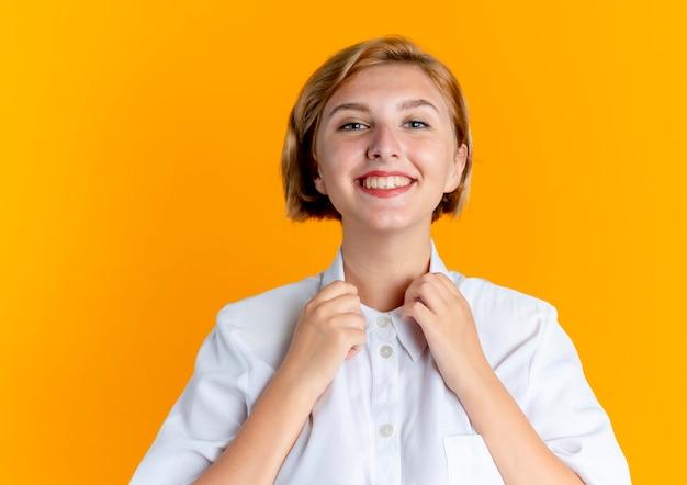 젊은 웃는 금발 러시아 여자 보유 칼라 복사 공간이 오렌지 배경에 고립