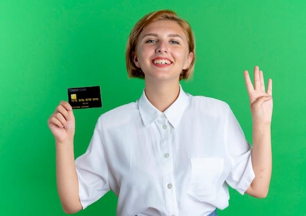 Молодая улыбающаяся русская блондинка держит кредитную карту и жестами четыре