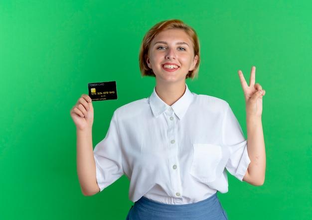 Giovane ragazza russa bionda sorridente tiene la carta di credito e gesti il segno della mano di vittoria