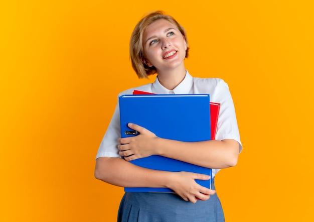 Молодая улыбающаяся белокурая русская девушка держит папки с файлами, глядя вверх, изолированные на оранжевом фоне с копией пространства