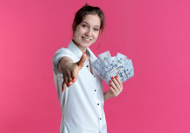 Молодая улыбающаяся русская блондинка протягивает руку, держа деньги на розовом с копией пространства