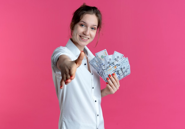 Young smiling blonde russian girl holds hand out holding money on pink  with copy space