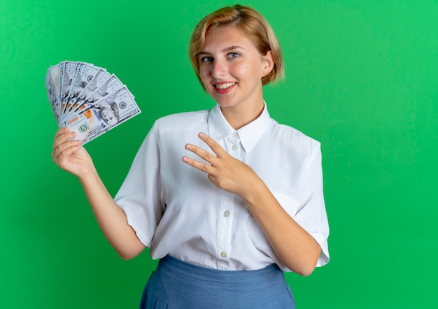Young smiling blonde russian girl holds money and gestures three with fingers