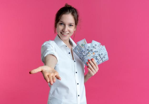 Молодая улыбающаяся русская блондинка держит деньги, протягивая руку на розовом с копией пространства