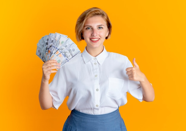 Young smiling blonde russian girl holds money and thumbs up isolated on orange background with copy space