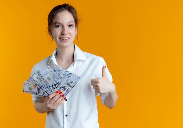 La giovane ragazza russa bionda sorridente tiene i pollici dei soldi sull'arancia con lo spazio della copia