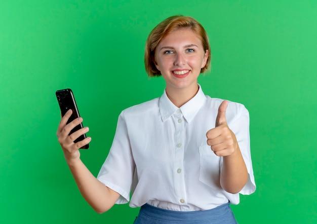 La giovane ragazza russa bionda sorridente tiene i pollici del telefono in alto isolato su priorità bassa verde con lo spazio della copia
