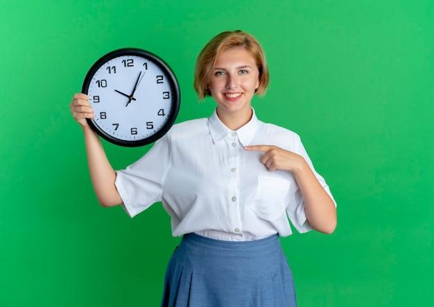 La giovane ragazza russa bionda sorridente tiene e indica l'orologio isolato su priorità bassa verde con lo spazio della copia