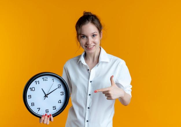 La giovane ragazza russa bionda sorridente tiene e indica l'orologio isolato sullo spazio arancione con lo spazio della copia