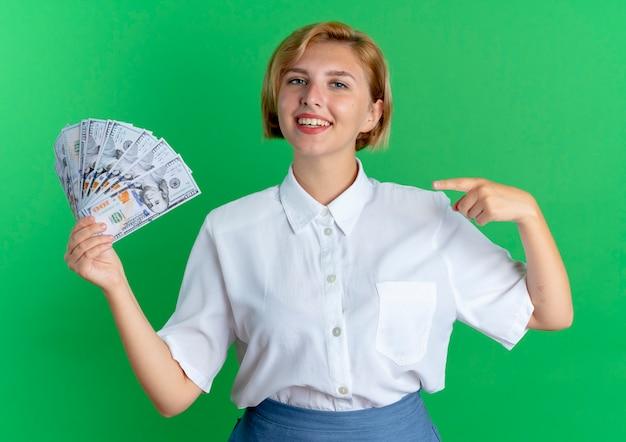 La giovane ragazza russa bionda sorridente tiene e indica i soldi isolati su spazio verde con lo spazio della copia