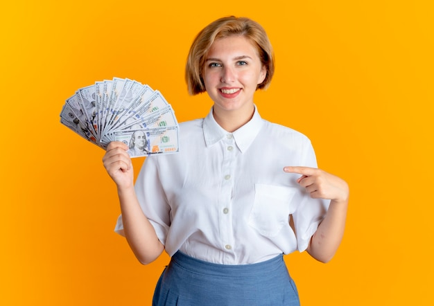 Young smiling blonde russian girl holds and points at money isolated on orange background with copy space