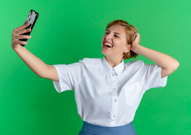 Молодая улыбающаяся русская блондинка смотрит на телефон, принимая селфи, кладет руку на голову