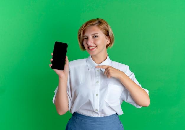 Молодая улыбающаяся русская блондинка указывает на телефон, изолированный на зеленом фоне с копией пространства