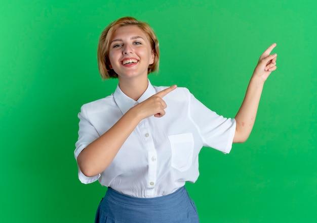 La giovane ragazza russa bionda sorridente indica il lato isolato su priorità bassa verde con lo spazio della copia