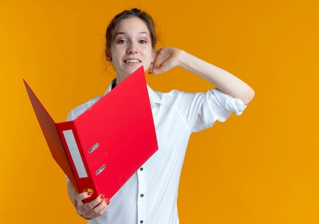 Молодая улыбающаяся русская блондинка кладет руку за голову, держа папку с файлами
