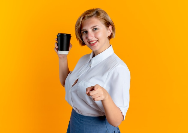 Young smiling blonde russian girl stands sideways holding coffee cup and pointing at camera