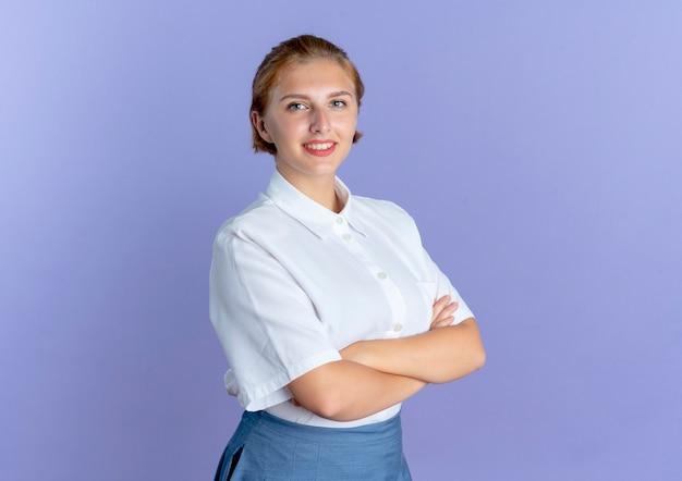 Молодая улыбающаяся русская блондинка стоит со скрещенными руками, изолированными на фиолетовом фоне с копией пространства