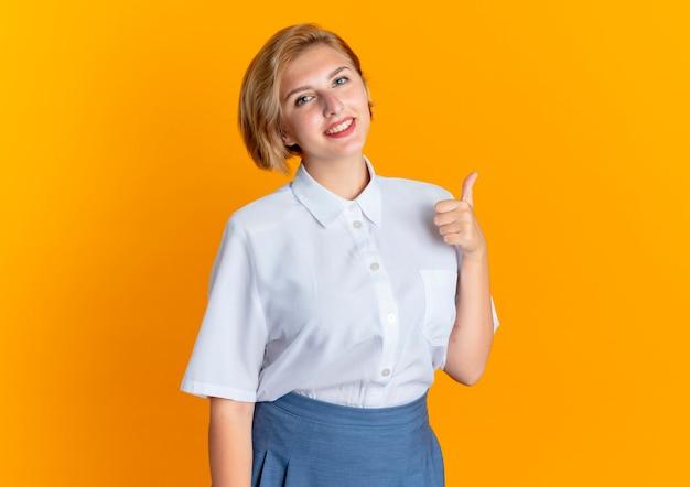 Молодая улыбающаяся русская блондинка показывает палец вверх на оранжевом фоне с копией пространства