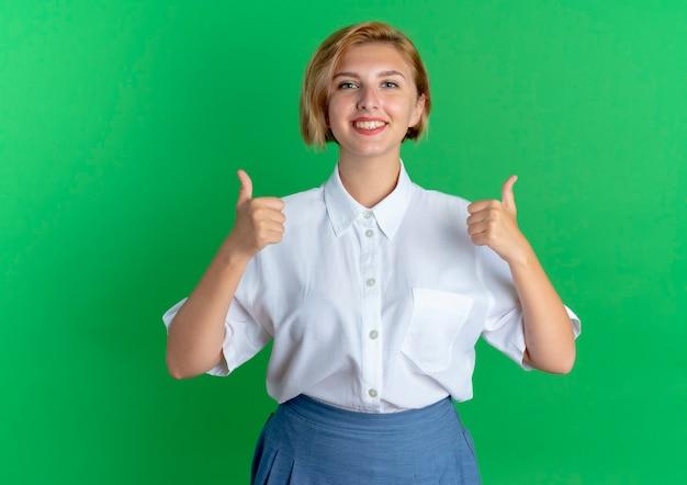 Молодая улыбающаяся русская блондинка показывает палец вверх двумя руками, изолированными на зеленом фоне с копией пространства