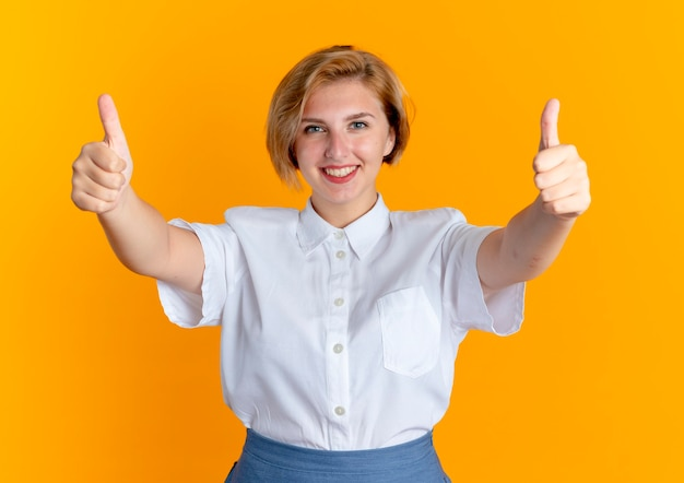 젊은 미소 금발 러시아 여자 엄지 손가락 복사 공간 오렌지 배경에 고립 된 두 손으로