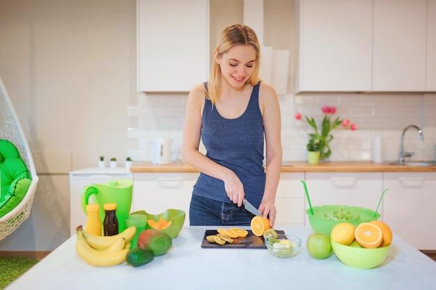 Молодая усмехаясь белокурая женщина варя свежие фрукты в кухне. здоровая пища. вегетарианская еда. диета детокс