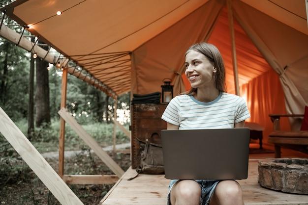 Молодая улыбающаяся белокурая женщина, сидящая на глэмпинге, набрав на ноутбуке, потоковое, обмен сообщениями. кемпинговый образ жизни. малобюджетные путешествия. концепция удаленной работы. современные коммуникационные технологии в интернете.