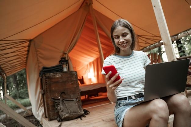 Молодая улыбающаяся белокурая женщина, сидящая на глэмпинге, с помощью ноутбука и обмена сообщениями на смартфоне. кемпинговый образ жизни. малобюджетные путешествия. концепция удаленной работы. современные коммуникационные технологии в интернете.