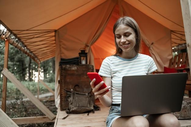 Молодая улыбающаяся белокурая женщина, сидящая на глэмпинге с помощью ноутбука и говорящая на смартфоне. кемпинговый образ жизни. малобюджетные путешествия. концепция удаленной работы. современные коммуникационные технологии в интернете.