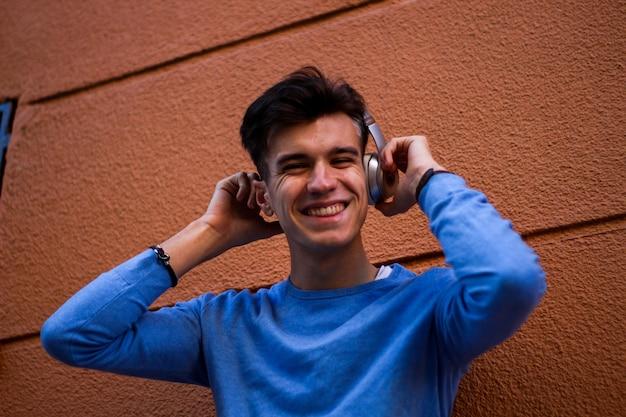 オレンジ色の壁にヘッドフォンで若い笑顔の少年