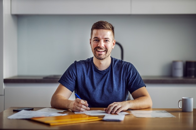 Young smiling breaded man sitting at dining table and filling in monthly bills